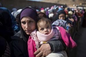 ©ACNUR A. McConnell. Mujeres y niños recién llegados hacen cola para el registro y distribución de ayuda en la ciudad de Arsal, Líbano, el 17 de febrero de 2014
