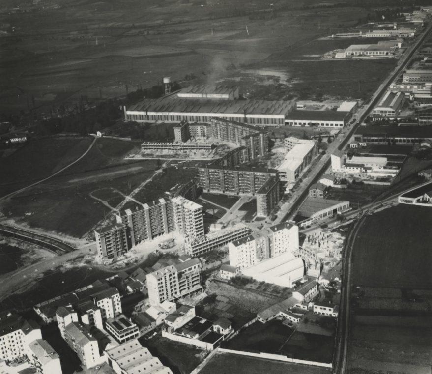 """Vista aérea de los primeros bloques del barrio hacia 1963. En la foto se pueden ver el antiguo edificio de la Central Lechera en construcción y el Garaje """"Alas"""". Fondo Fundación Sancho el Sabio."""